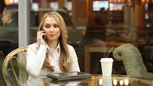 dívka mluví po telefonu v kavárně. mávl rukou na pozdrav. čekání do přátel