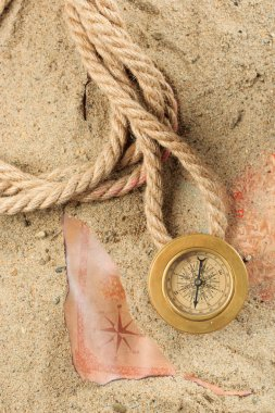 set of nautical instruments, lying on the sand and old map. concept adventure
