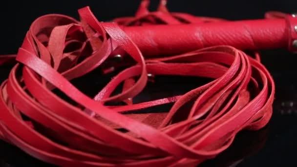 červený kožený bič na Bdsm hry. na černém pozadí. erotická hračka