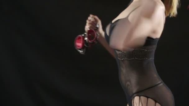 Busty Mädchen in Dessous zeigt rote Handschellen. auf schwarzem Hintergrund. Sex-Spielzeug. rote Lederpeitsche