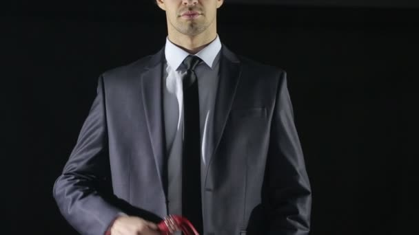 man in a business suit holding a whip for sex games. red skin. love toys
