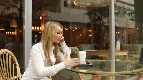 businesswoman swears on the phone sitting in a cafe. It uses a Tablet PC