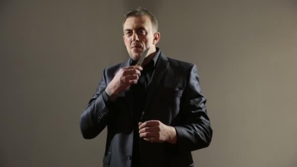 männlichen Gangster in einem Business-Anzug mit einem Messer. halten Sie die Klinge an den Hals