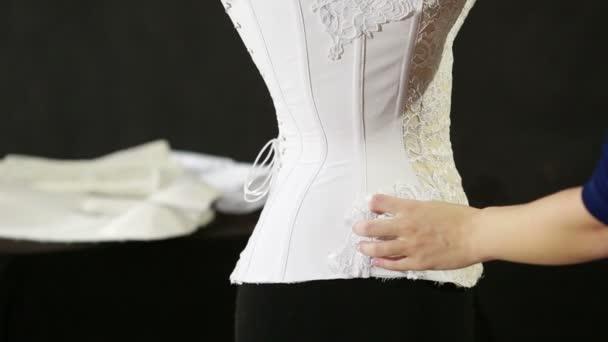 Korzet na šněrování v výrobní závod spodní prádlo. Výroba spodního prádla, vázání krajkový korzet švadlena. bílý korzet