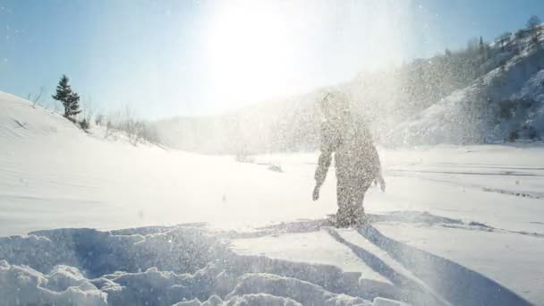 Young woman throwing snow on blue sky in background - happines emotions