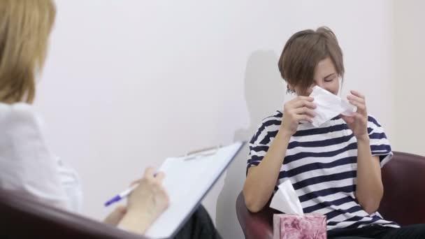 Ženské psycholog dělat poznámky během relace psychologické terapie. smutná dívka