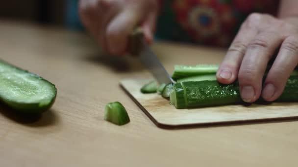 Babička nakrájí okurku. Ženské ruce krájejí zelenou okurku na kuchyňském stole