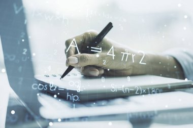 Double exposure of creative scientific formula concept with hand writing in notebook on background with laptop, research and development concept