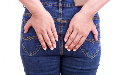 Woman's hand holding the backside : Concept hemorrhoids