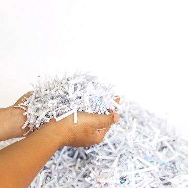 Hand holding Scrap Paper from paper cutter
