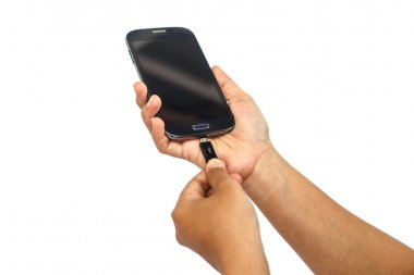 Hand holding smartphone and connect charger isolated on white ba