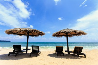 Sun umbrella and sun loungers stand at the beach in Phuket, Thai