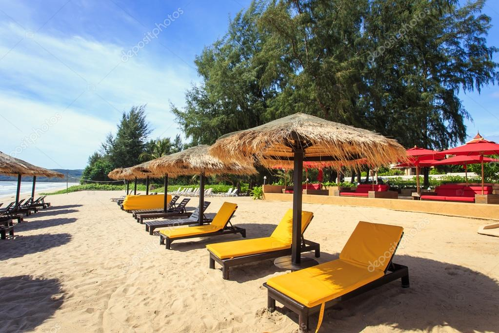 Sun umbrella and sun loungers stand at the beach in Phuket, Thai