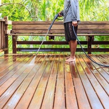 Thai man do a pressure washing on timber