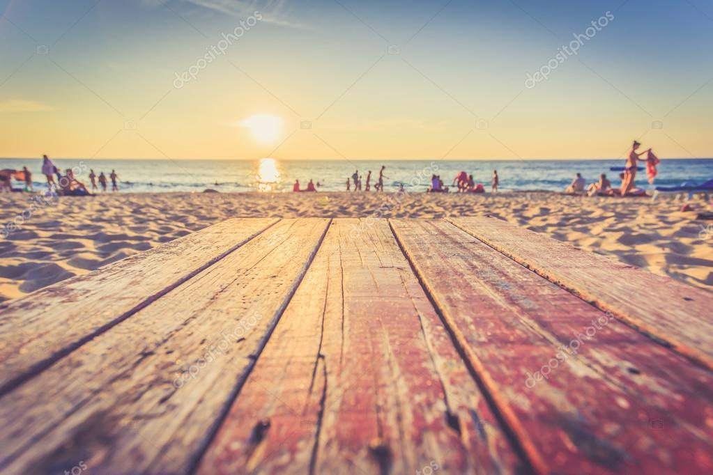 Wooden table at sunset beach