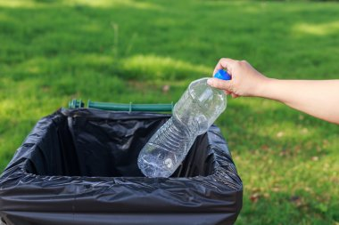 Hand throwing plastic bottle
