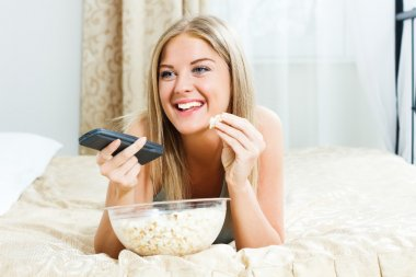 Woman lying on her bed,eating popcorn and watching tv