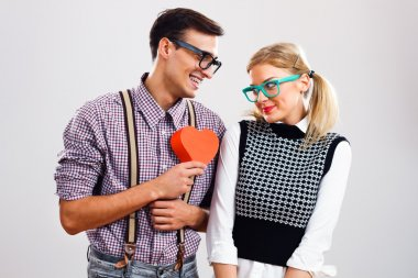 Nerdy man is about to give a red heart to his nerdy lady