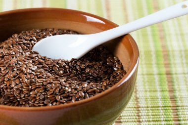 Brown flax seeds in brown green bowl