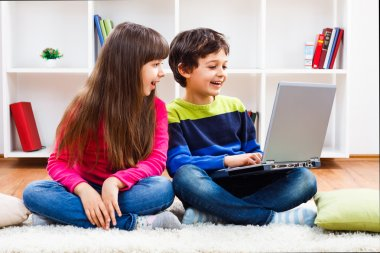 Cute little girl and little boy are using laptop
