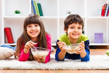 Cute little girl and little boy are eating cereals