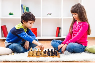 Little boy and little girl are playing chess
