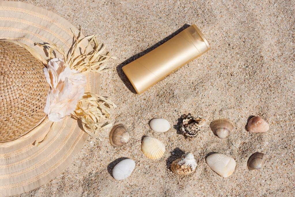 Suntan lotion bottle with straw hat, shells and rocks in the sand