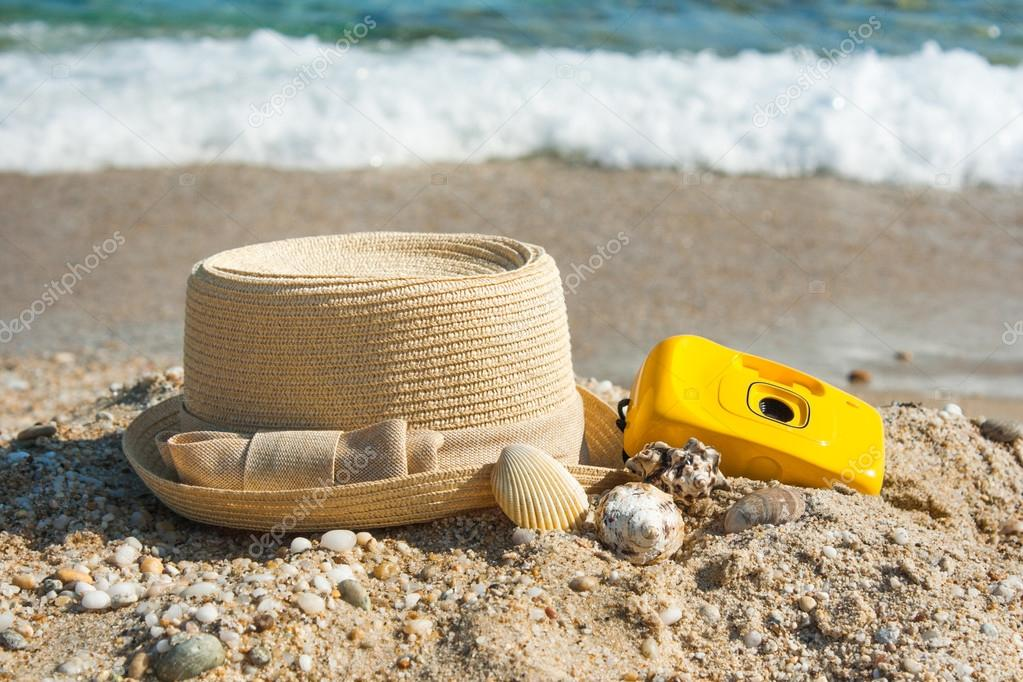 hat and camera on the beach