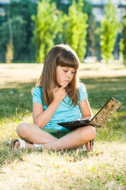 Beautiful little girl sitting in park with her laptop