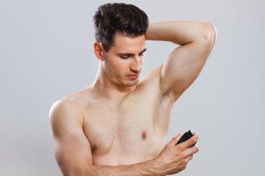 Handsome man using deodorant