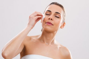Woman is cleaning her face