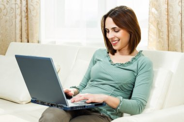 Woman sitting on sofa at her home and using laptop