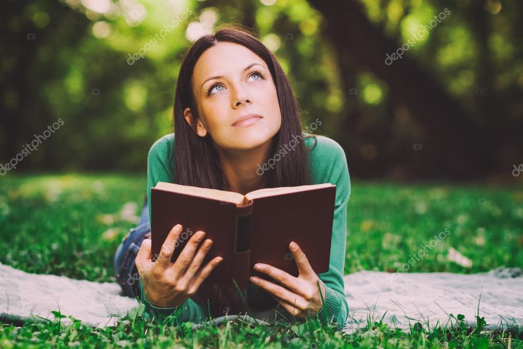 Woman is thinking about something while reading a book