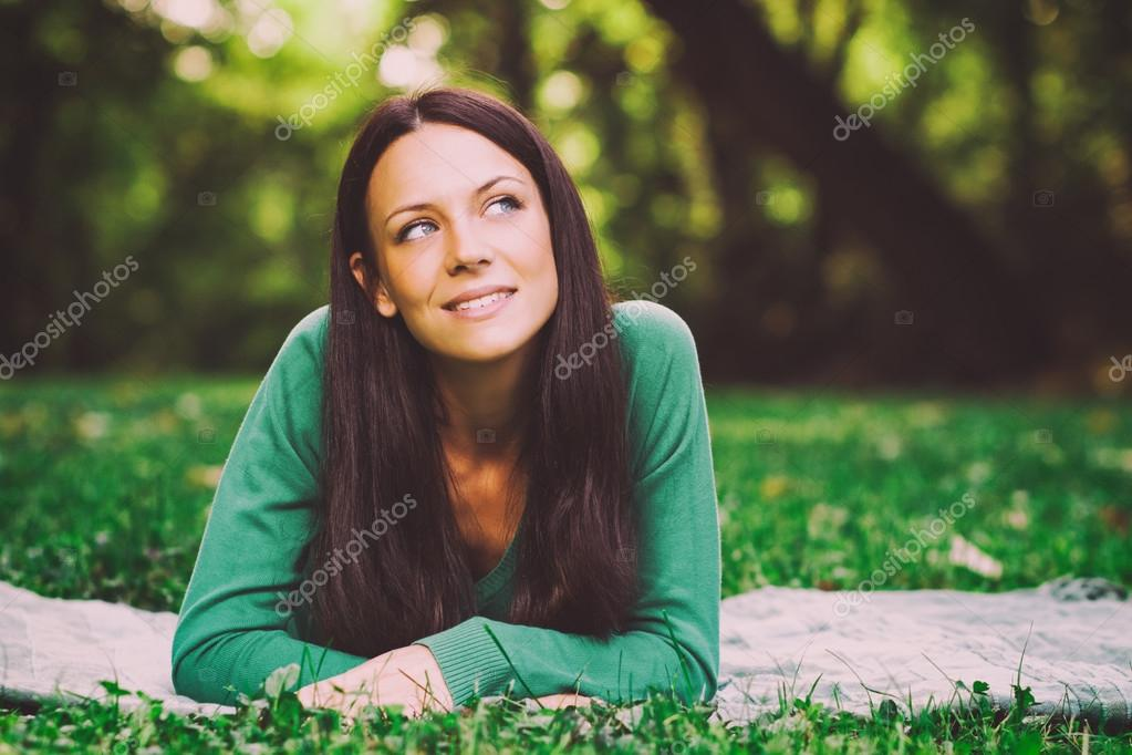 Woman lying down in nature and thinking about something