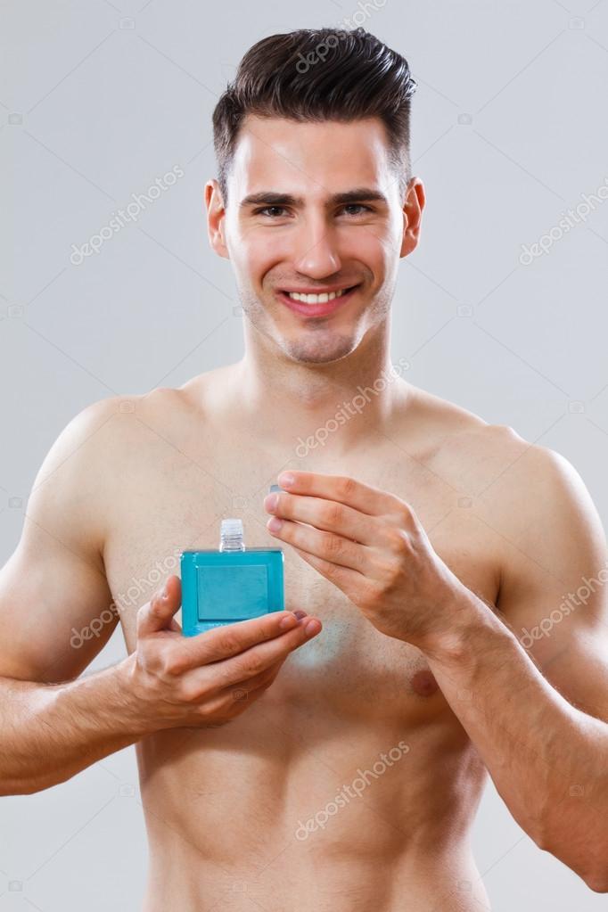 Portrait of handsome man holding aftershave