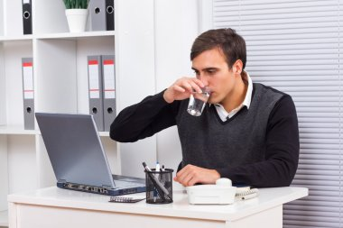 Business sitting in his office,working and drinking water