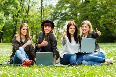 Girls are showing thumbs up while they are using laptop