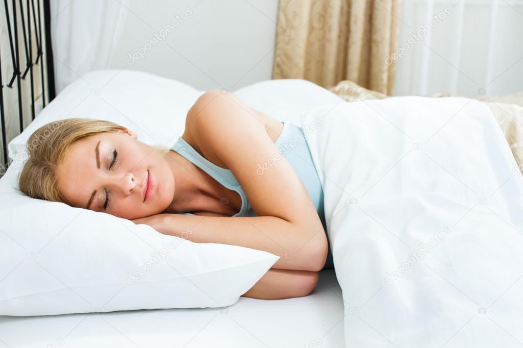 blonde woman is sleeping in her bedroom