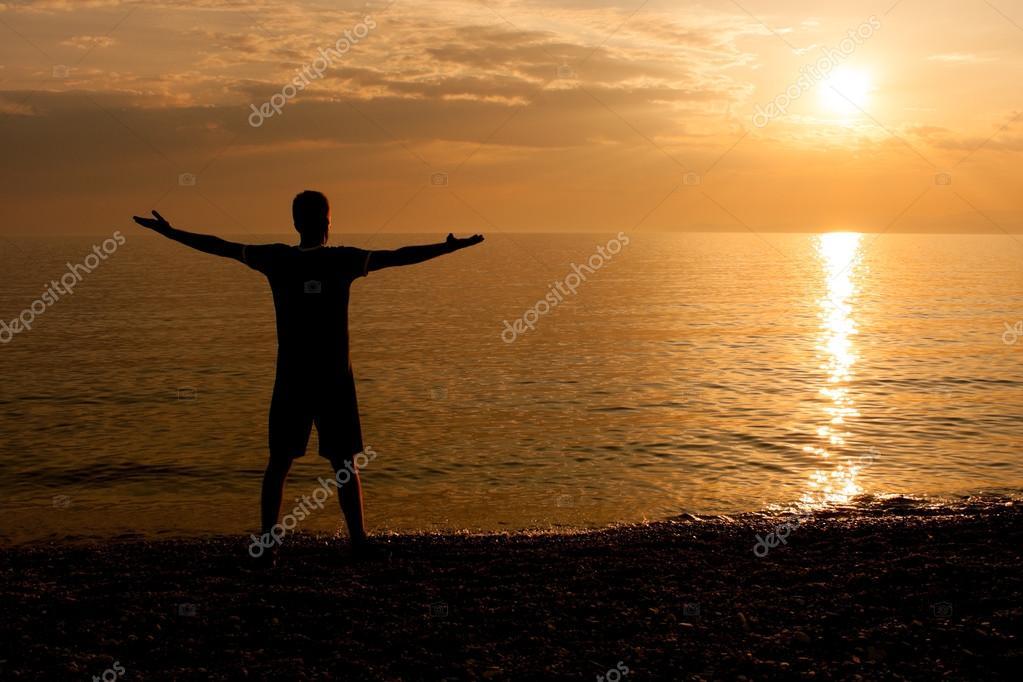 Happy man enjoys in sunset