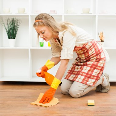 Young housewife cleaning floor