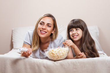 Mother and daughter watching tv and eating popcorn together on bed stock vector