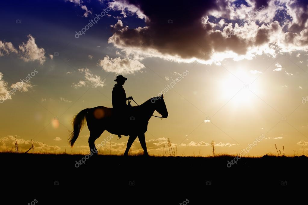 Ranch hand on horse at sunset