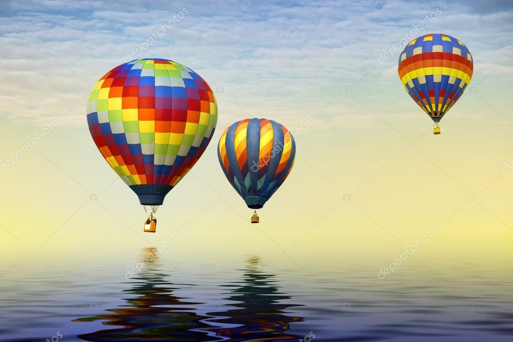 Three hot air balloons over water