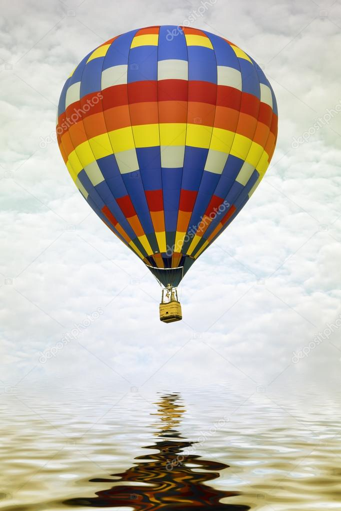 Colorful hot air balloon reflecting in water