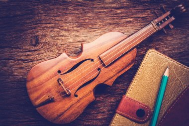 Violin and notebook with pencil on grunge dark wood background