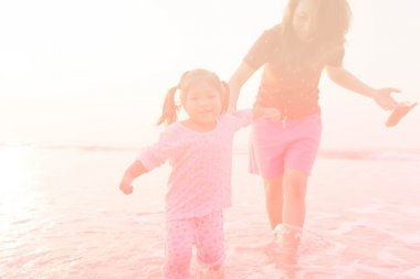 Abstract blurred Mother and children playing on the sunset beach