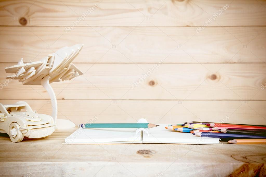 Libro abierto y lápices de colores sobre tabla de madera, decoración ...