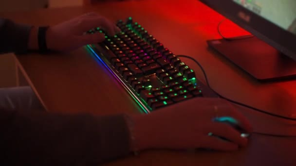 Computer gamer sitting at the table in front of powerful PC and playing cyber video games using colorful mouse and computer keyboard with RGB backlit illumination. Keyboard with neon lights for