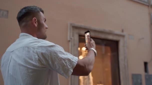 Rückansicht eines gutaussehenden Mannes, der auf einer uralten Straße mit majestätischen Gebäuden und einer schönen mittelalterlichen Fassade spaziert, männliche Touristen, die Fotos und Videos mit dem Handy machen, Erinnerungen an die Reise