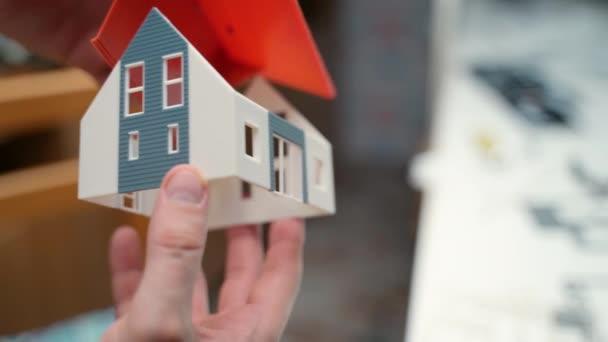Detailní záběr miniaturního plastového domu v rukou profesionálního projektanta, malý model stavby pro budoucí realizaci. Projekt nového domu, příprava na koupi nemovitosti